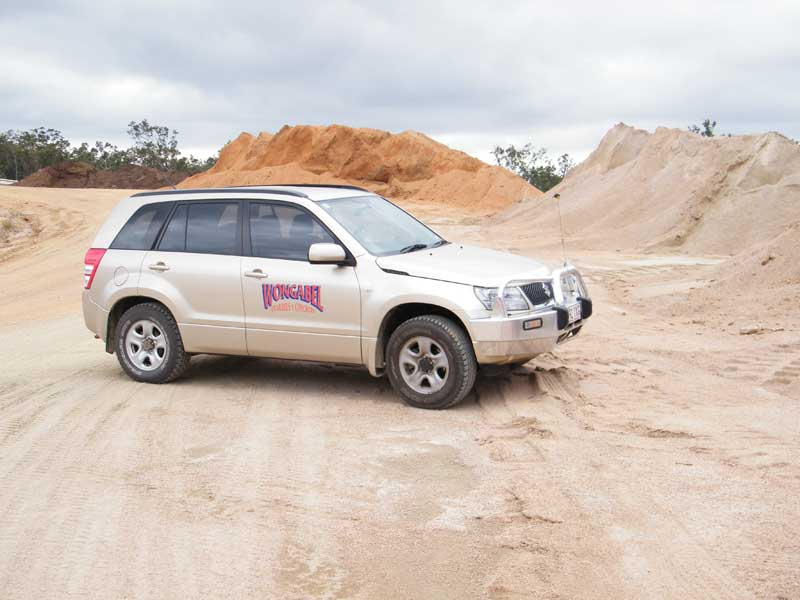 Company vehicle parked in front of Quarry stockpiles at Wongabel Quarry